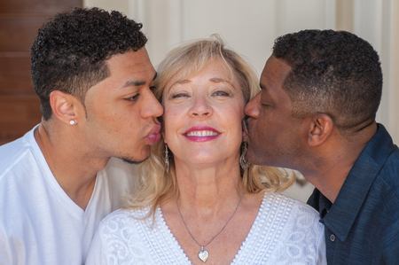 multiracial family: Tight view of multiracial family planting kiss on mom.