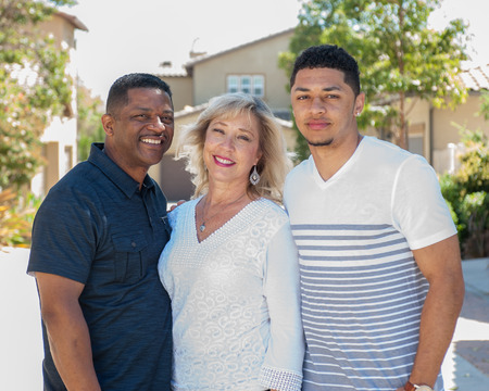 multiracial family: Half body view of multiracial family in backyard with mom in middle.