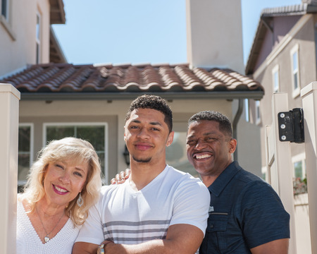 multiracial family: Tight view of multiracial family in backyard with son in middle.