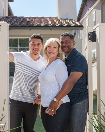 three quarter: Three quarter view of multiracial family in backyard with mom in middle.