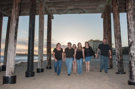 pilings: Famle walking together under Ventura Pier at sunset. Stock Photo
