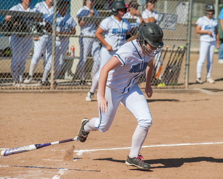 softball player: High school softball player running to first base.
