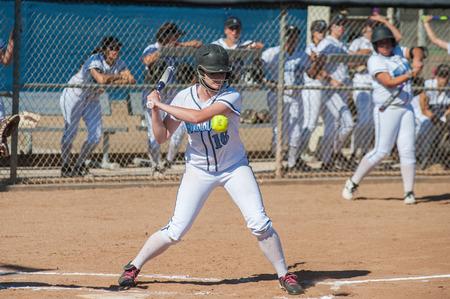 softball player: High school softball player taking the high pitch.