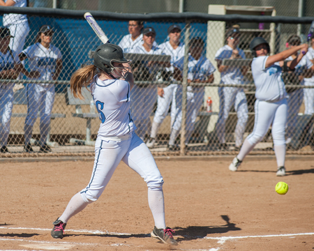 High school softball player hitting a ground ball.