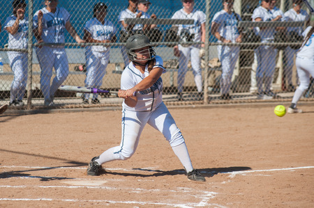 softball player: Asian teen softball player taking a swing.