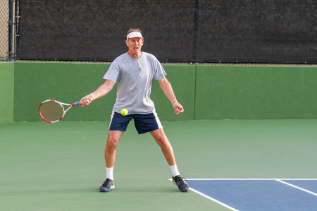 forehand: Senior age man showing perfect open forehand stance. Stock Photo