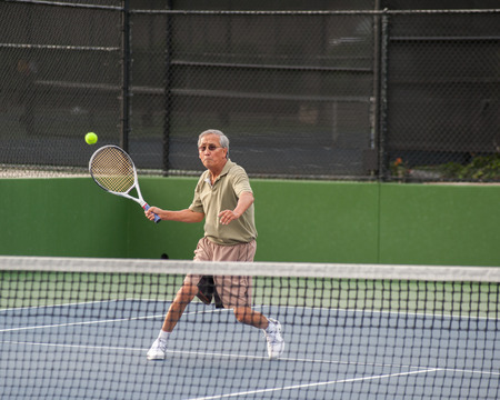 forehand: Chinese senior concentrating on the forehand volley. Stock Photo