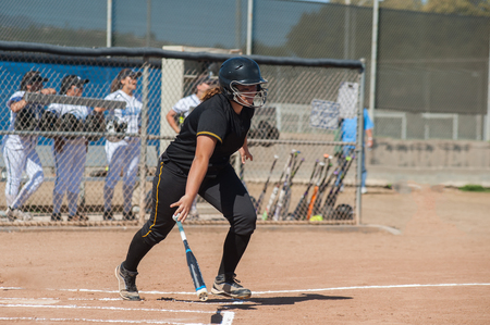 double game: Strong softball player in black uniform dropping the bat while running to first. Stock Photo