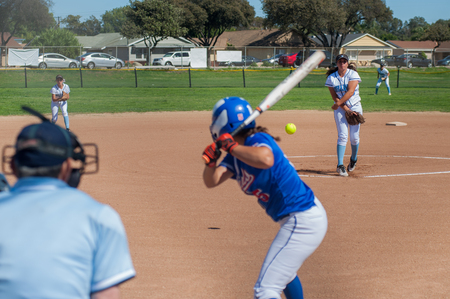 innings: Softball pitcher throwing the curve ball to the batter.