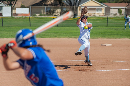 Close up of softball pitcher winding up to throw the curve ball to the batter. Imagens
