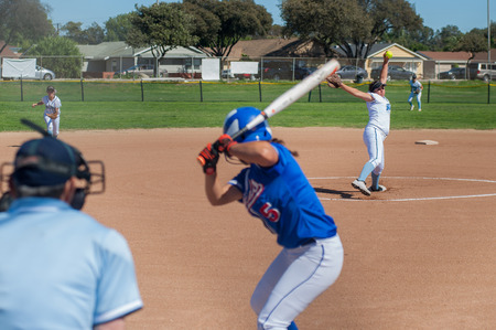innings: Softball pitcher winding up to throw the curve ball to the batter.