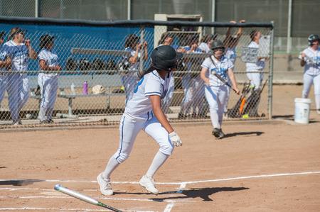 batter: Filipino softball batter running to first base. Stock Photo