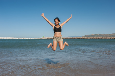 Young and energetic Latina beauty jumping over ocean water. Stock Photo
