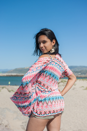 over the shoulder: Latina woman looking over shoulder at beach. Stock Photo