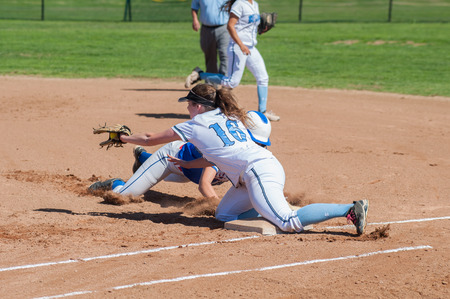 innings: Softball runner and defense player collide at first base. Stock Photo