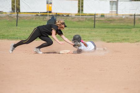 softball player: Black uniform softball player tagging the player sliding in white.