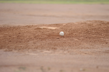 innings: Baseball sitting on the pitching mound dirt.