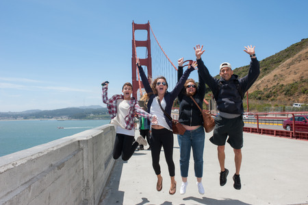 Mother and Father jumping with their two daughters at Golden Gate Bridge.