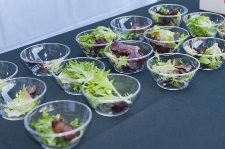 Salade voorgerechten gerangschikt in kleine, plastic kommen. Stockfoto