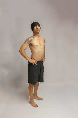 middle age man: Muscular middle age man with tattoo standing with hands on hips.