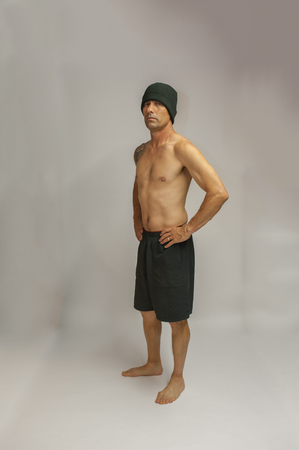 middle age man: Muscular middle age man with tattoo standing facing left with hands on hips. Stock Photo