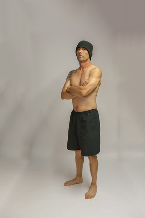 middle age man: Muscular middle age man with tattoo standing with arms crossed facing left.