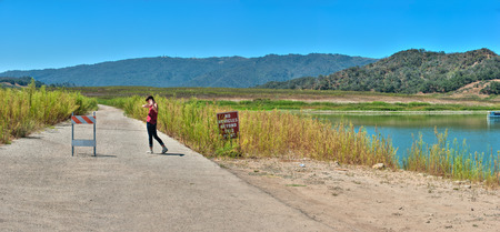 barricade: Teenage girl standing on old Highway 150 barricade at low Lake Casitas. Stock Photo