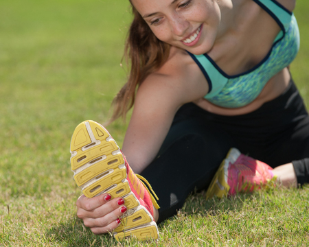 grab: Smiling teenage runner stretching to grab her soles. Stock Photo