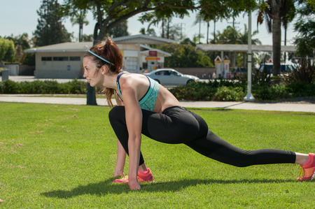Flexible female athlete stretching her hip flexor in side view.