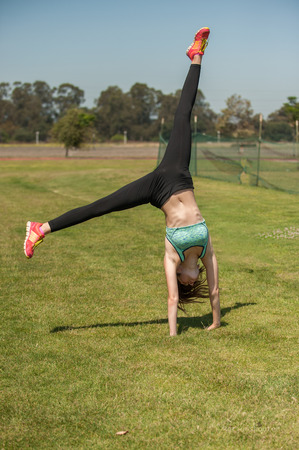 Female athlete in black tights finishing a cartwheel. Stock Photo - 61839869