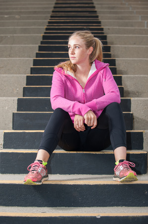 concrete steps: Attractive blond sitting on concrete steps looking to left.