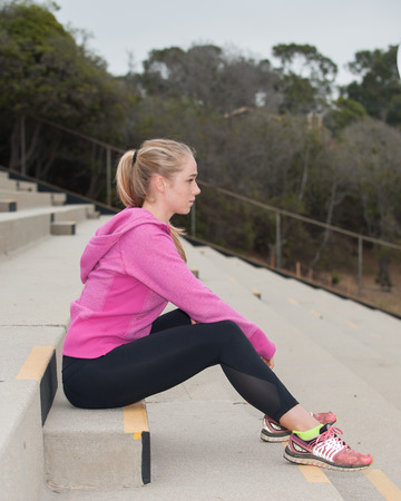 concrete steps: Blond athlete sitting on concrete steps looking forward.