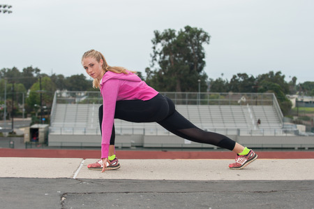 lunge: Athlete in black tights lunge stretching over the stadium while looking left. Stock Photo