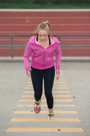 cardiovascular workout: Pretty blond looking down while running up stadium.