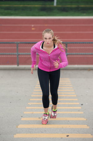 Pretty blond looking up while running up stadium. Stock Photo