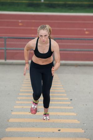 intense: Intense female athlete in black tights running stadium stairs.
