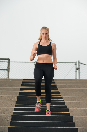 descending: Intense female athlete in black tights descending stadium stairs.