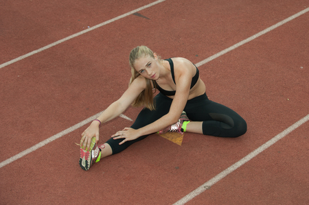 hamstrings: Attractive blond athlete stretching hamstrings on the track.