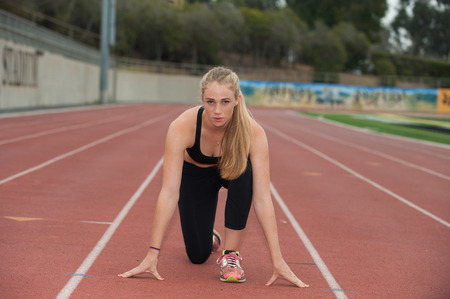 crouched: Sprinter in black tights crouched on the track. Stock Photo