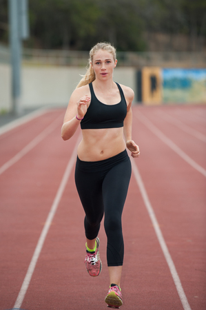 pace: Blond female runner in black tights at a steady pace. Stock Photo