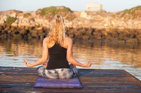 sukhasana: Athletic female seated on dock with hands in Sukhasana pose while facing away. Stock Photo
