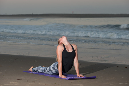 breaking waves: Peaceful Cobra Yoga pose with head back near breaking waves of Pacific Ocean. Stock Photo