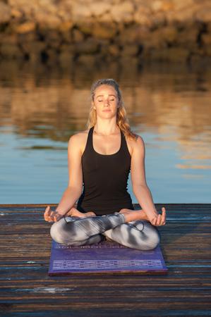 sukhasana: Athletic female with eyes closed, seated on dock with hands in Sukhasana pose.