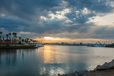 Stormy clouds over Ventura Harbor mouth lets spot of sun down on kayaker.