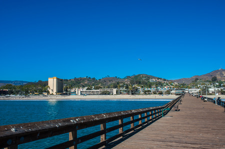 Stroll down Ventura Pier on sunny day with hotel in distance.