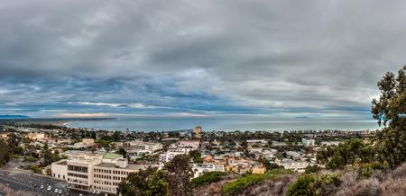 Ominous rain clouds moving over panoramic city of Ventura as sun rises.