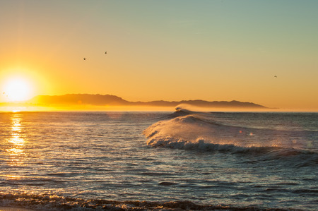 glows: Morning sun glows as east winds blow tops of waves at Ventura beach. Stock Photo