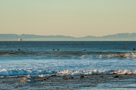 Surfers patiently waiting in lull between sets at Ventura beach with oil platform in background.