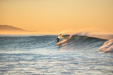 Morning sun glows off surfer as east winds blow tops of waves at Ventura beach. Stock Photo