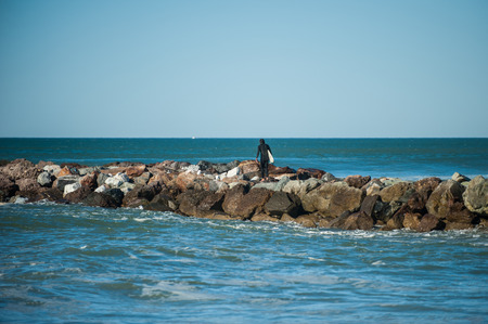 Adventurous surfer walking out on rock jetty to avoid paddling out to the waves. Stock Photo
